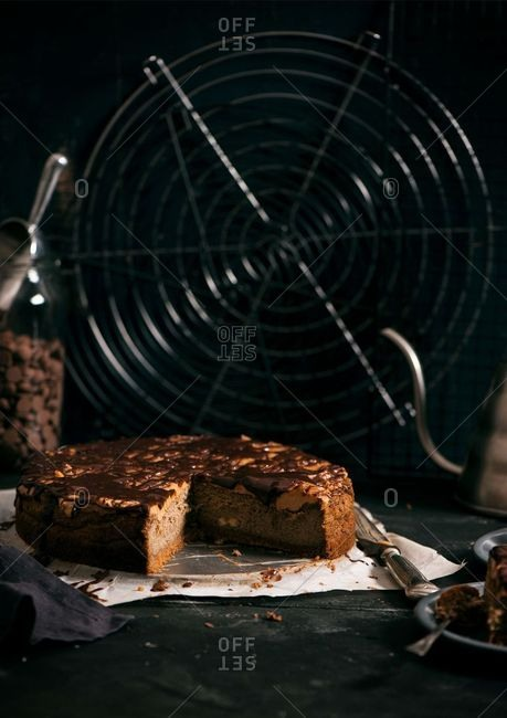 Slices missing from a chocolate drizzled cake in front of a fan