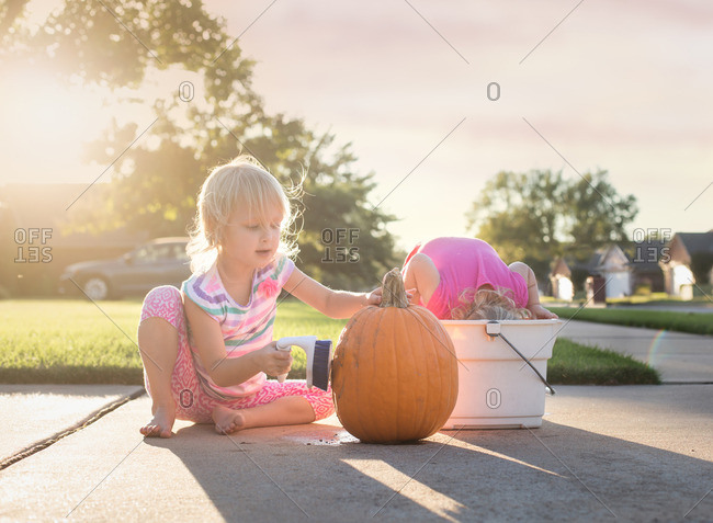 Two sisters on a sidewalk cleaning a pumpkin