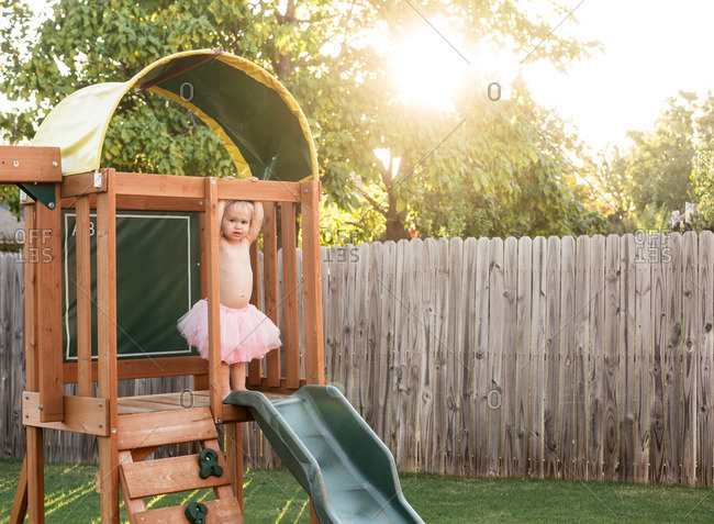 Little girl in a pink tutu standing on a backyard jungle gym