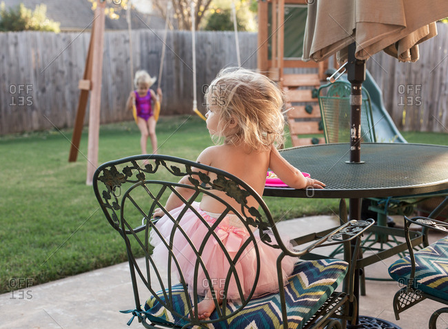 Girl in a tutu sitting at a patio table while her sister swings