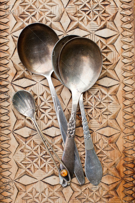 Antique silver spoons on a carved wooden tray