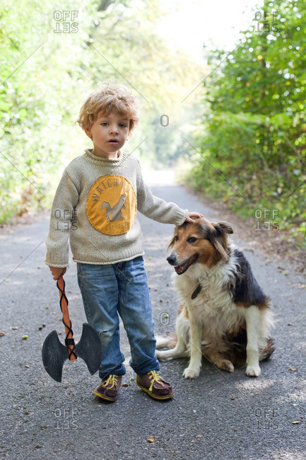 Boy on a nature trail petting his dog