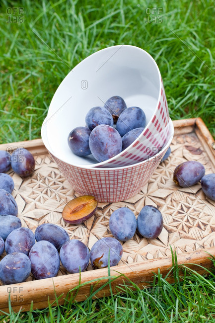 Plums in a ceramic serving bowl on a wooden tray