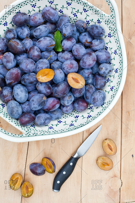 Fresh-picked plums in a large ceramic bowl