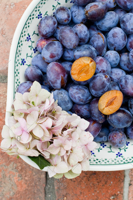 Plums and flowers in a ceramic bowl