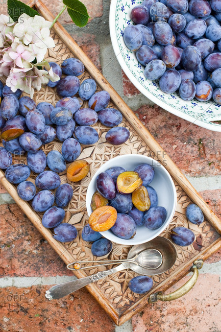 Plums in ceramic bowl and on a carved wooden tray
