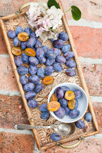 Carved wooden tray with plums and flowers on a brick surface