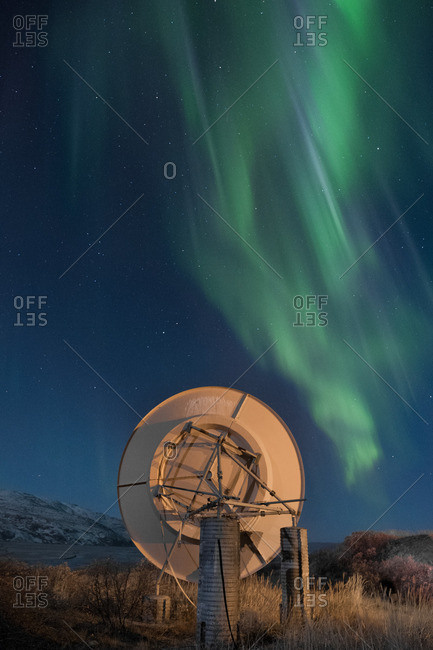 Aurora borealis over mountains and satellite dish in Greenland