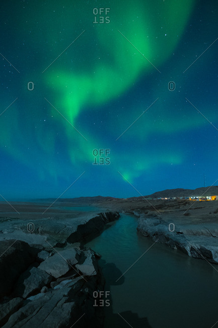 Aurora borealis over mountains and a river in Greenland