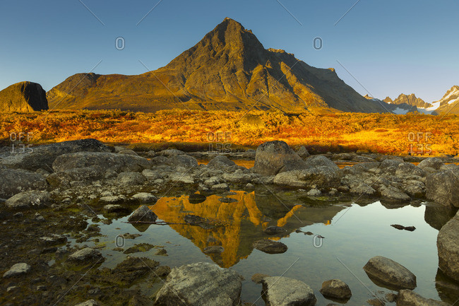 Mountain reflecting in a rocky lake at sunset in Greenland