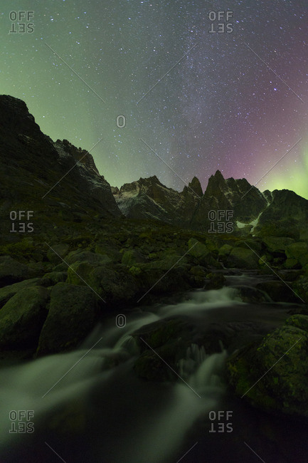 Aurora borealis over mountains and river in Greenland