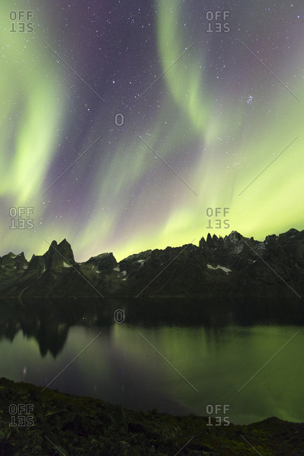 Northern lights over mountains and lake in Greenland