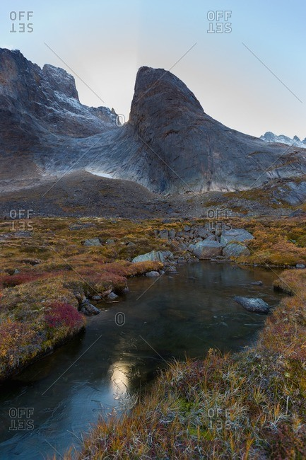 Partially frozen mountainside river in Greenland