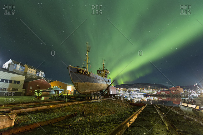 Aurora borealis over seaside town in Greenland