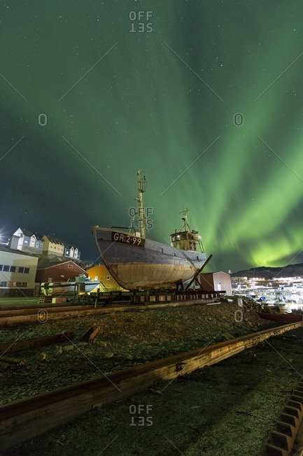 Aurora borealis over harbor side town in Greenland