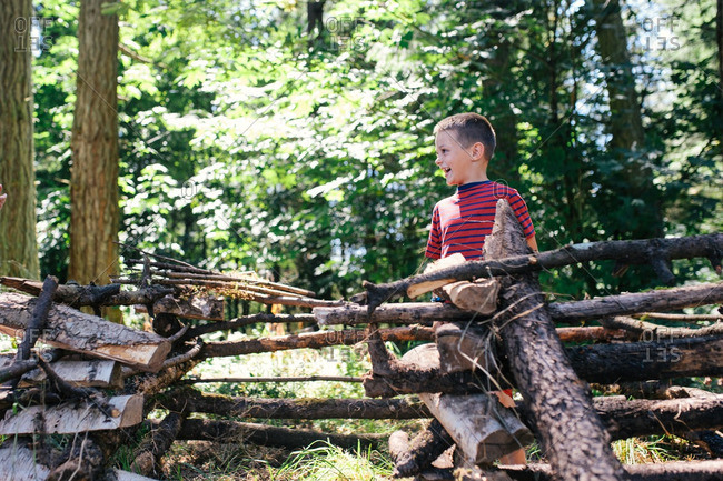 Boy standing behind a makeshift log fence smiling