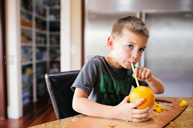 Boy sitting at a table drinking juice from a large orange