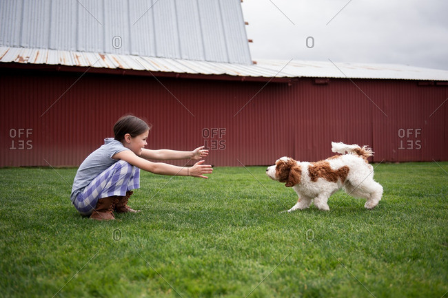 Girl reaching for her dog who is running toward her