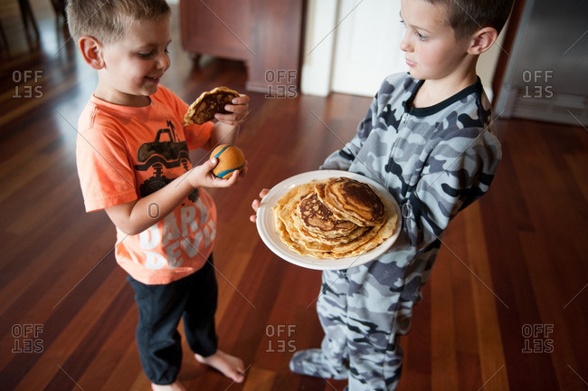 Two brothers in pajamas with a plate of pancakes