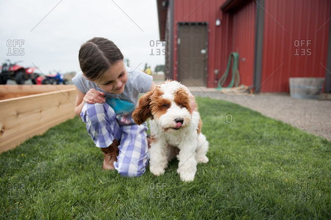 Girl on grass in front of a red barn hugging her dog