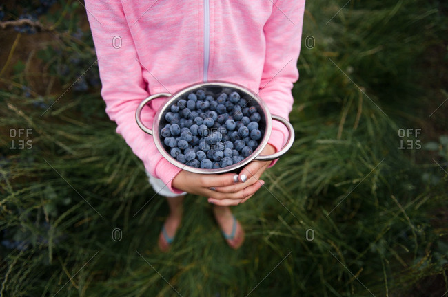 Little girl in a pink jacket holding a bowl of blueberries