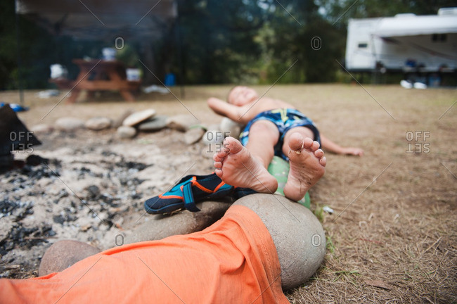 Boy in a bathing suit lying on stones beside a fire pit