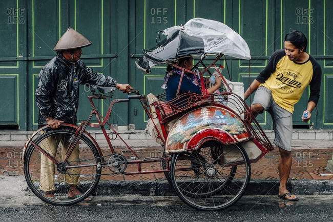Yogyakarta, Indonesia - January 24, 2016: A trishaw rider waiting for passengers to board a trishaw