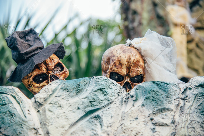 Close-up of skeletons decorations as bride and groom peeking over grave stones