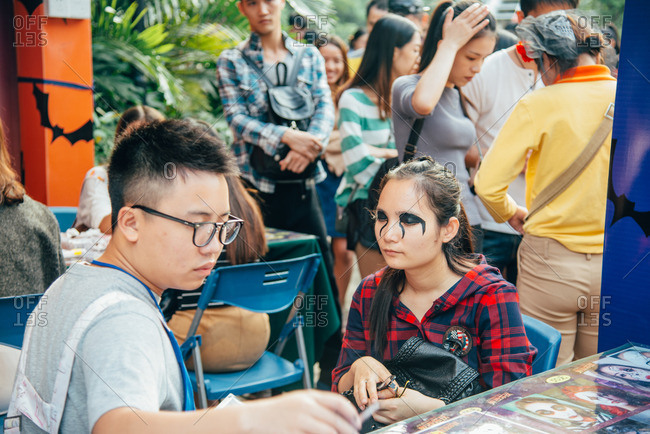 Guangzhou, China. - October 30, 2016: Woman getting her face painted in Halloween makeup