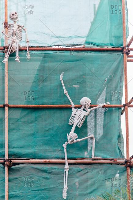 Skeleton decorations climbing an exterior wall