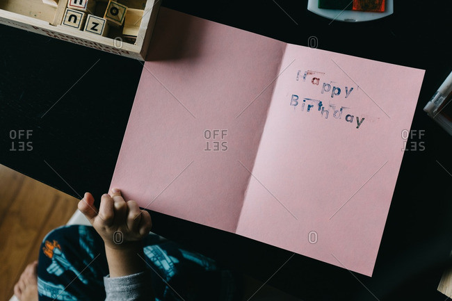 Child Makes Homemade Birthday Card With Stamps And Construction