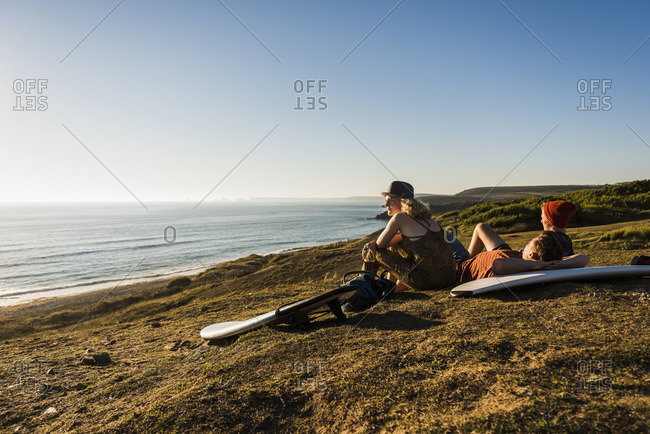 Three friends with surfboards relaxing at seaside