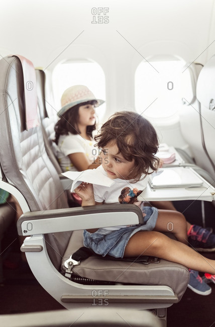 Two little girl flying on plane- playing with paperplane