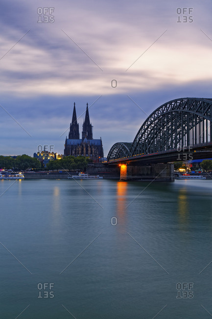 Germany- Cologne- view to Cologne Cathedral with Hohenzollern Bridge in the foreground at evening twilight