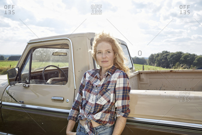 Portrait of strawberry blonde woman leaning against Pick Up