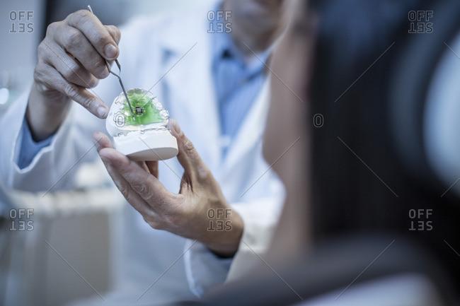 Dentist showing patient dental mold