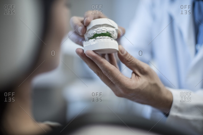 Orthodontist showing patient dental mold