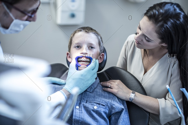 Boy with mother in dental surgery receiving orthodontic treatment