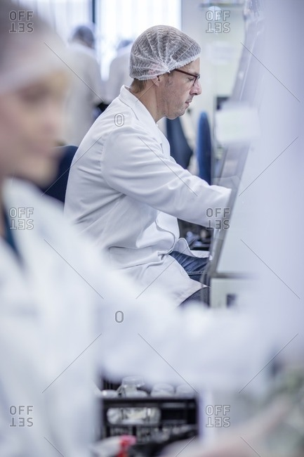 Scientists working in lab wearing protective clothing