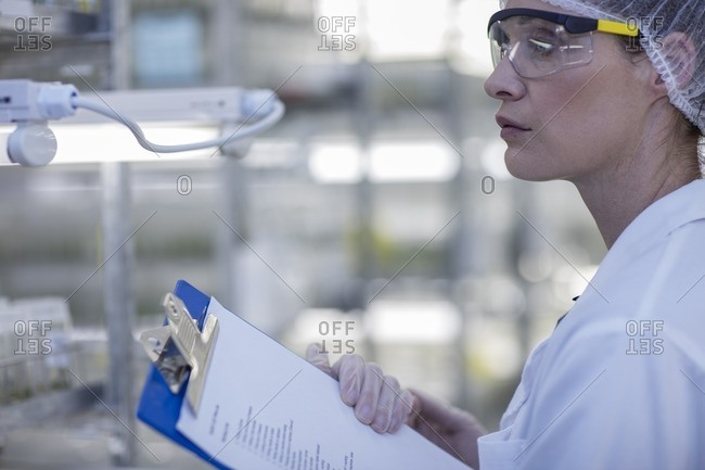 Woman wearing protective clothing in lab holding clipboard