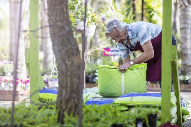 Elderly garde´ner stacking bags in garden centre