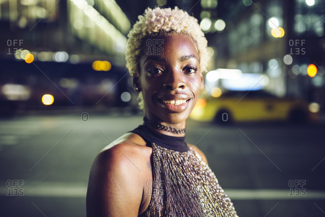 USA- New York City- portrait of happy young woman on Times Square at night