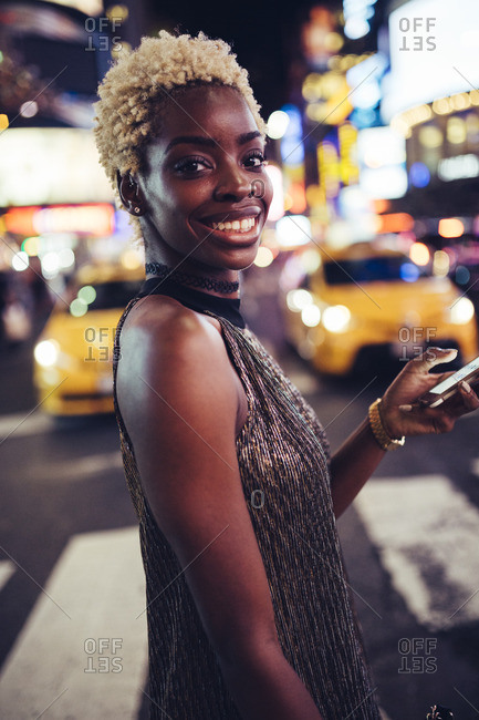USA- New York City- portrait of smiling young woman on Times Square at night