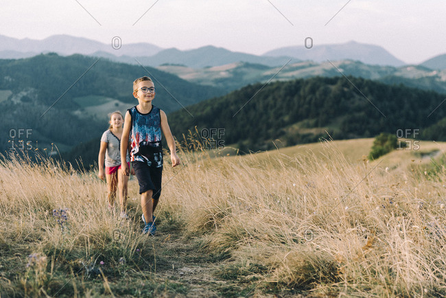 Italy- Gubbio- two children hiking at Apennine Mountains in the evening