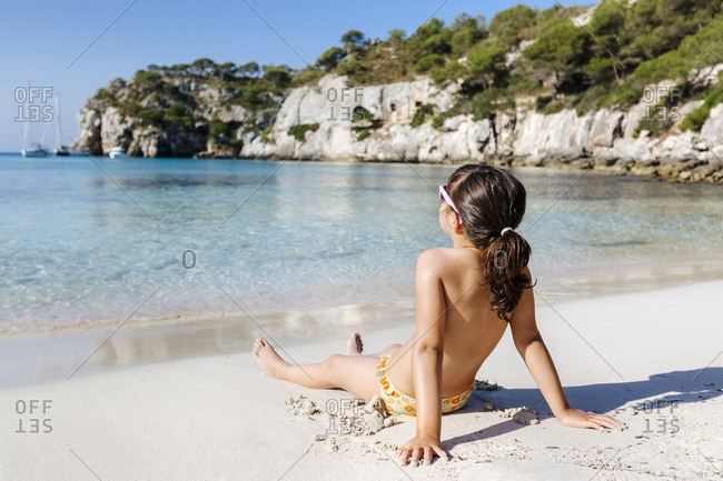 Little girl taking sunbath on the beach