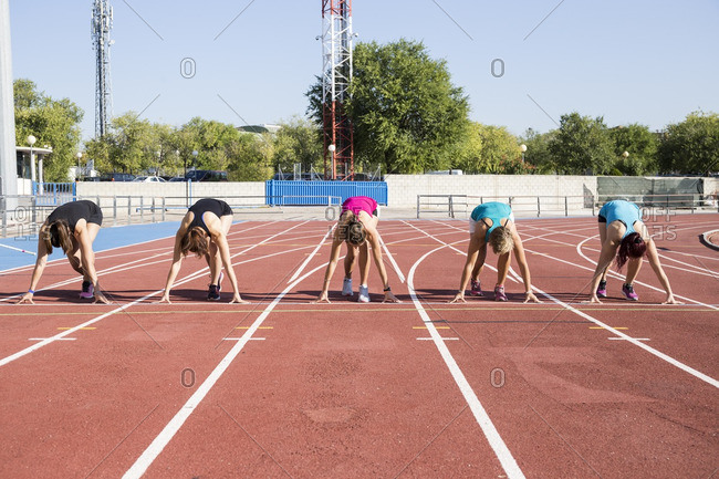 Female runners on tartan track in starting position