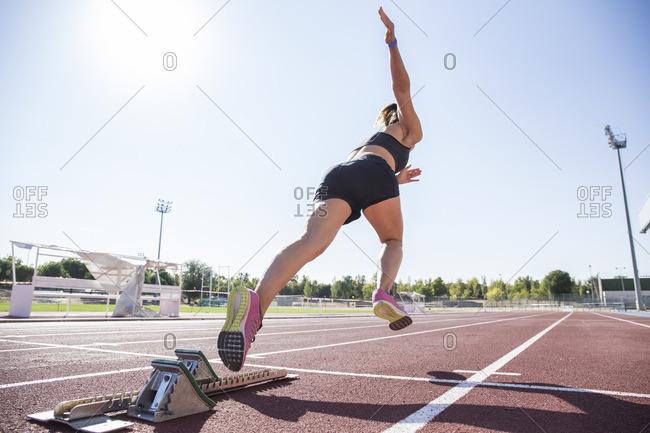 Female runner on tartan track starting