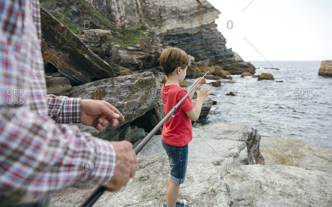 Grandfather and grandson fishing together at the sea
