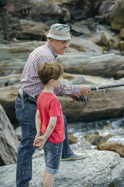 Grandfather and grandson fishing together at rock coast