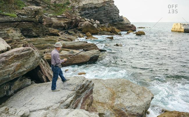 Senior man fishing at the sea